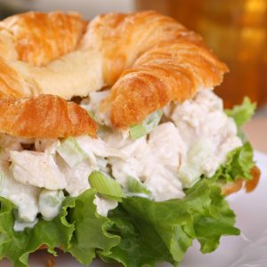 Closeup of a chicken salad and lettuce on a croissant roll