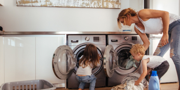 Mom does laundry as two toddler help mom load the dryer.