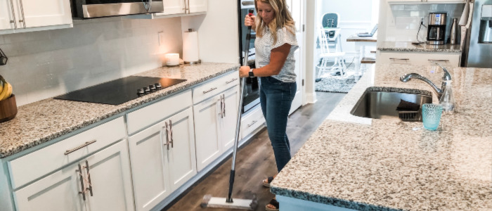 woman mops as she implements her home management routine.