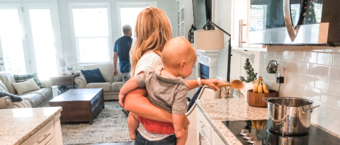 Mom implementing home management routines while she cooks with baby, and talks to husband walking away.