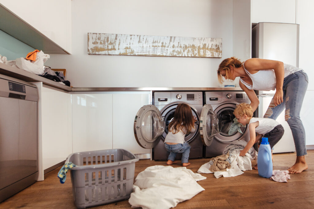 Mother teaching kids to load clothes in washing machine.