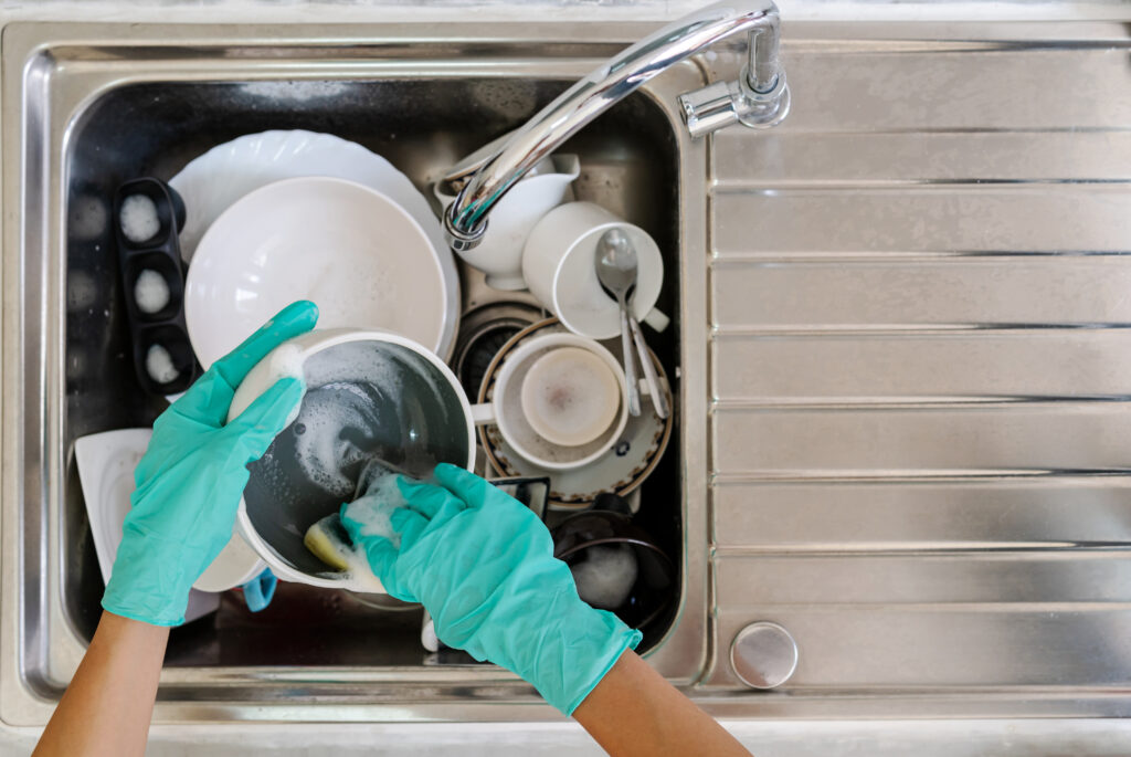 woman with gloves washing dishes in the kitchen.