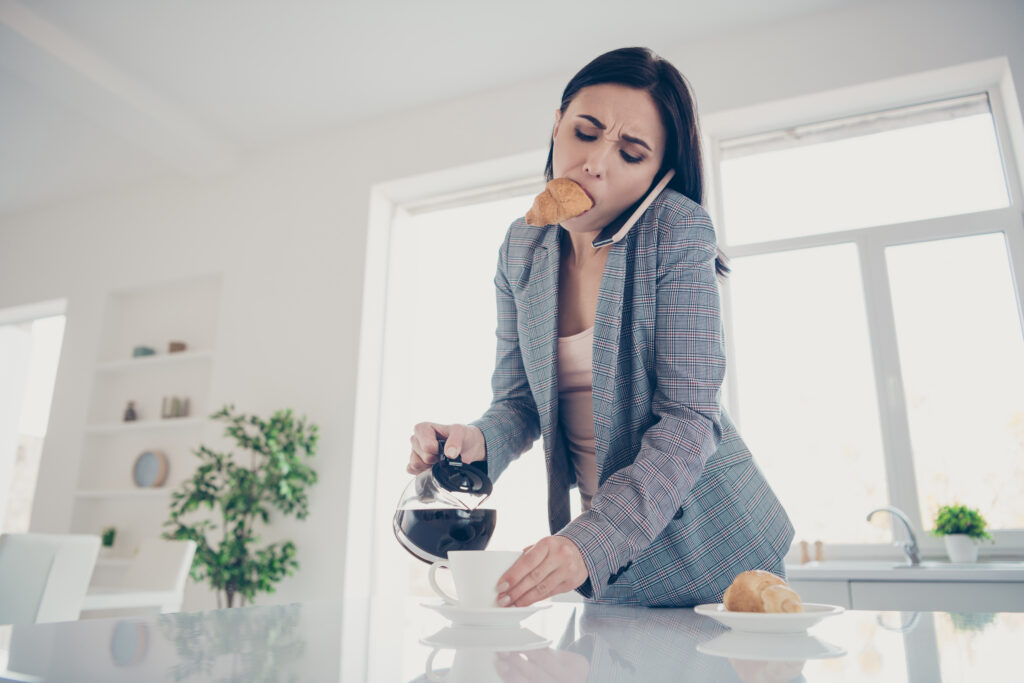 Close up tired women pouring a cup of hot beverage with a croissant inside her mouth late, while talking on cell phone and rushing to get to work.kitchen indoors