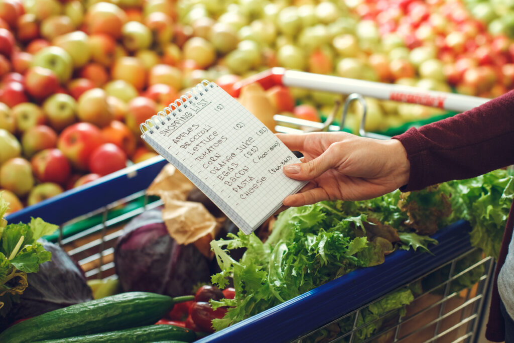 Woman shopping at the grocery store with a list.