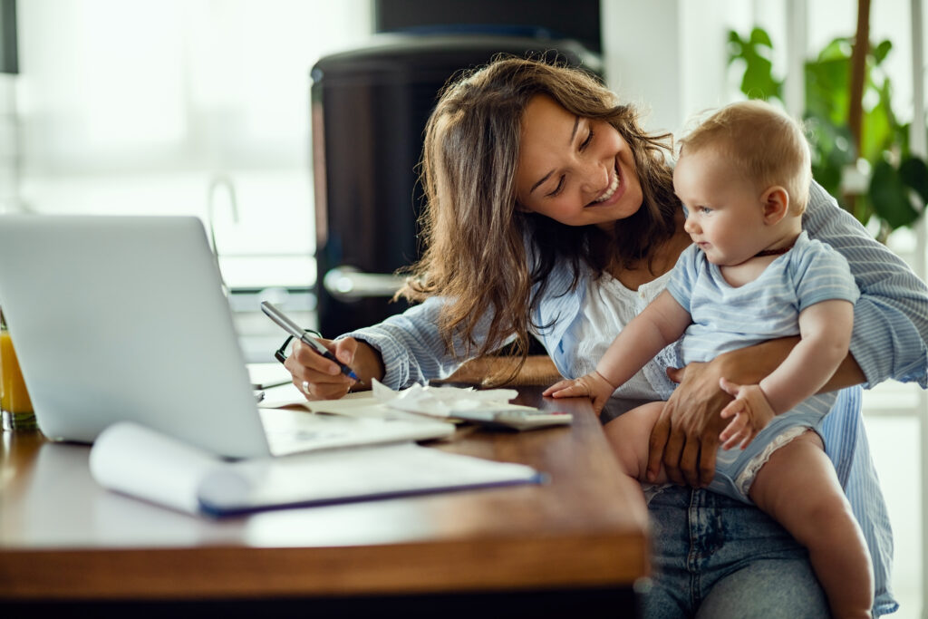 Young happy mother going through home finances with baby on her lap