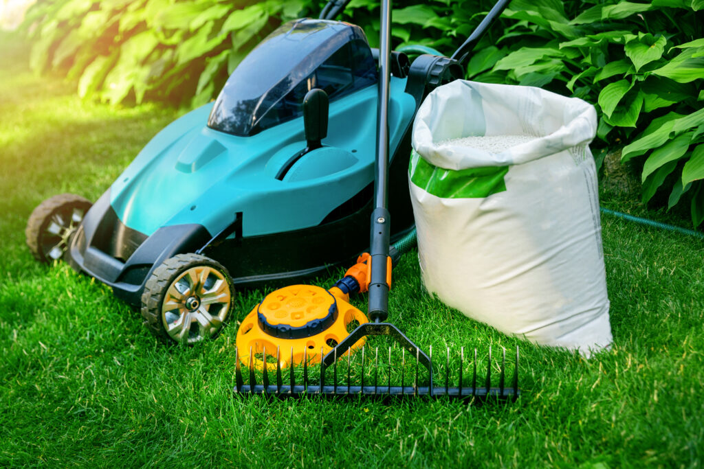 gardening tools and lawn care equipment on green grass