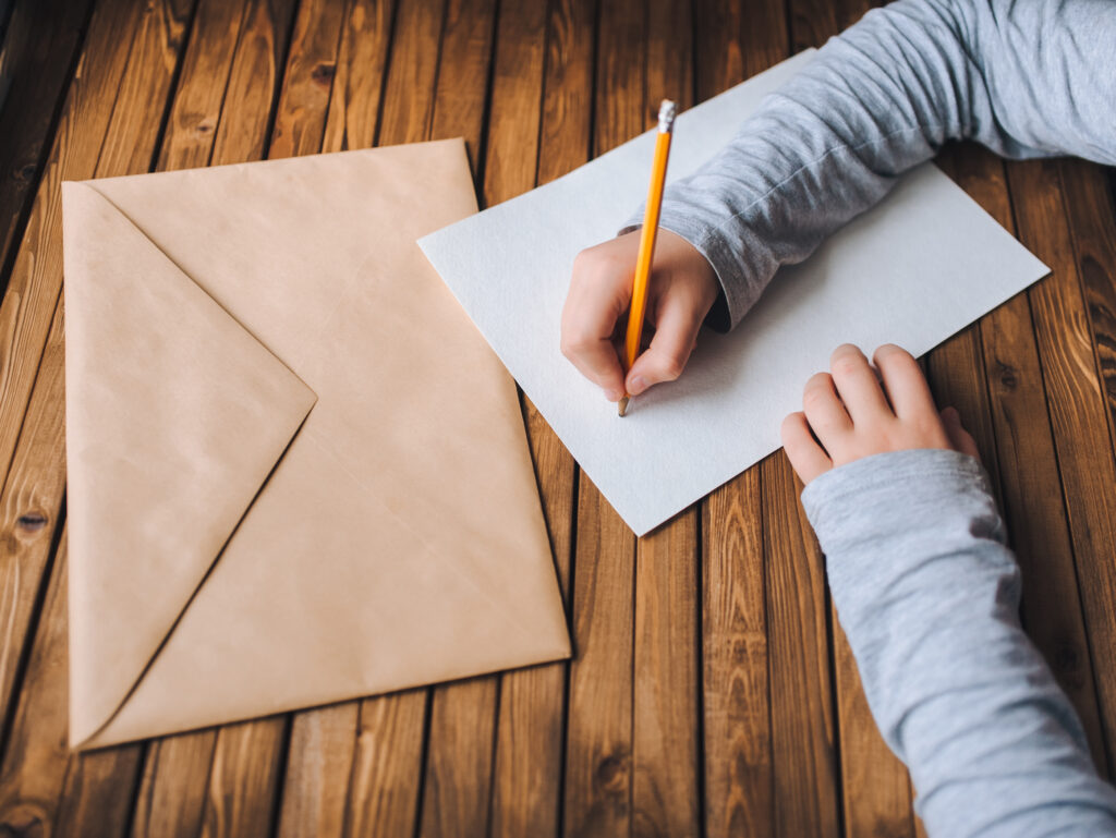 Children's hands write a letter. A brown envelope, a white sheet of paper and a pencil.