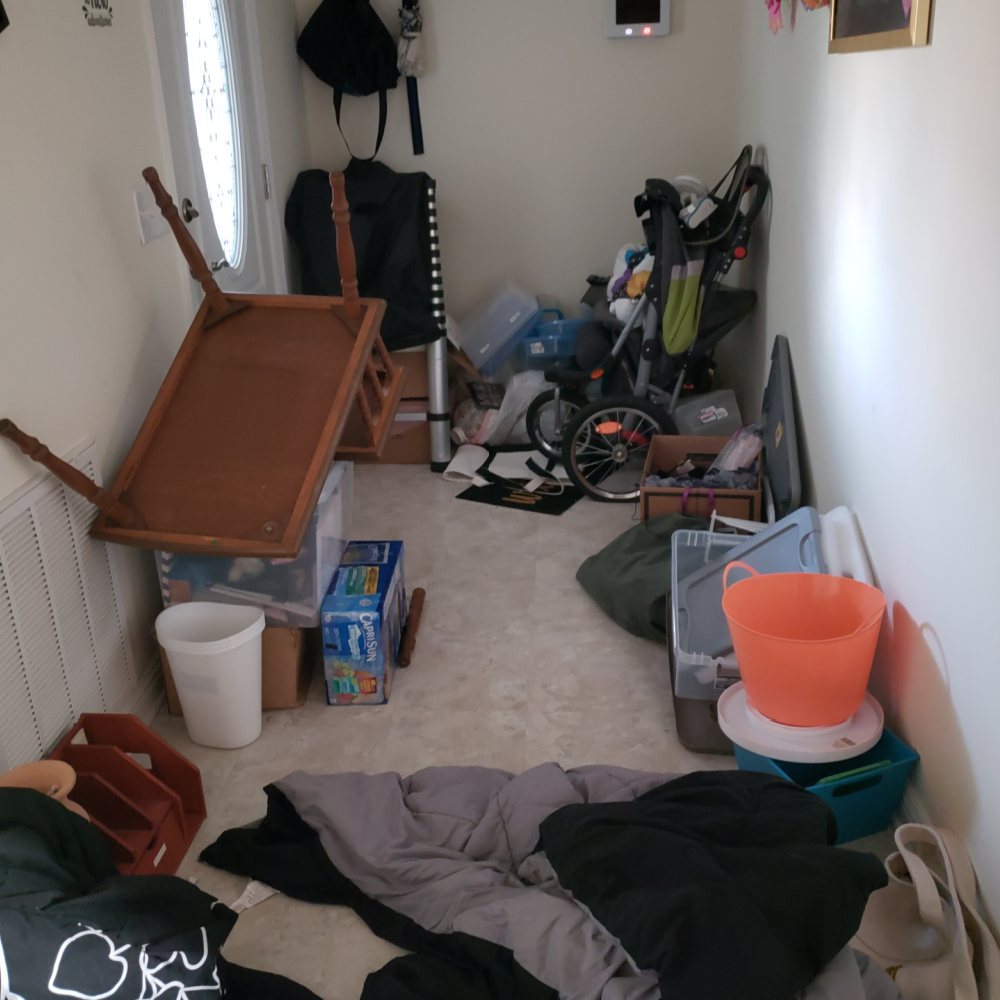 Messy House displaying a messy hallway or door entry with clothing, trash, organizing containers and broken furniture in this trashed house.