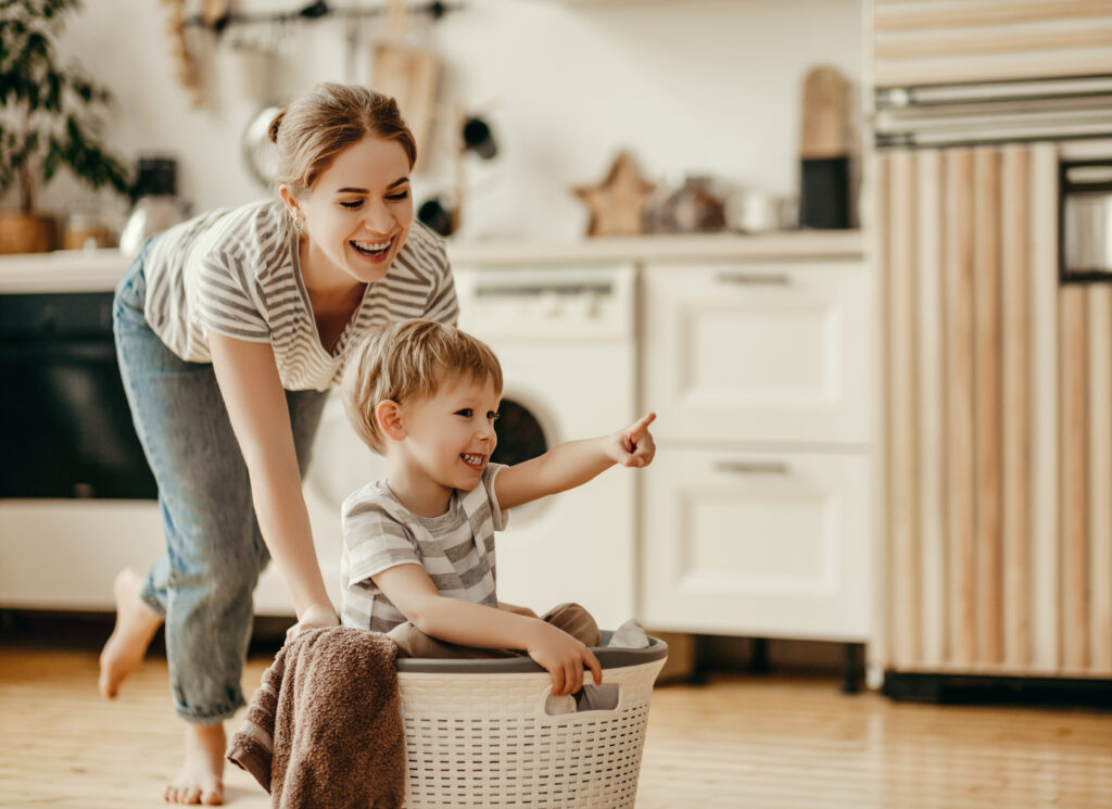mother and child son in laundry with washing machine
