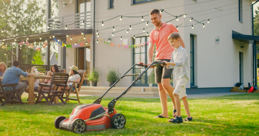 Father teaching son to mow the lawn.