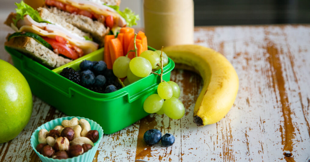 Picnic lunch ideas: Sandwich, grapes and carrots in a lunch box.