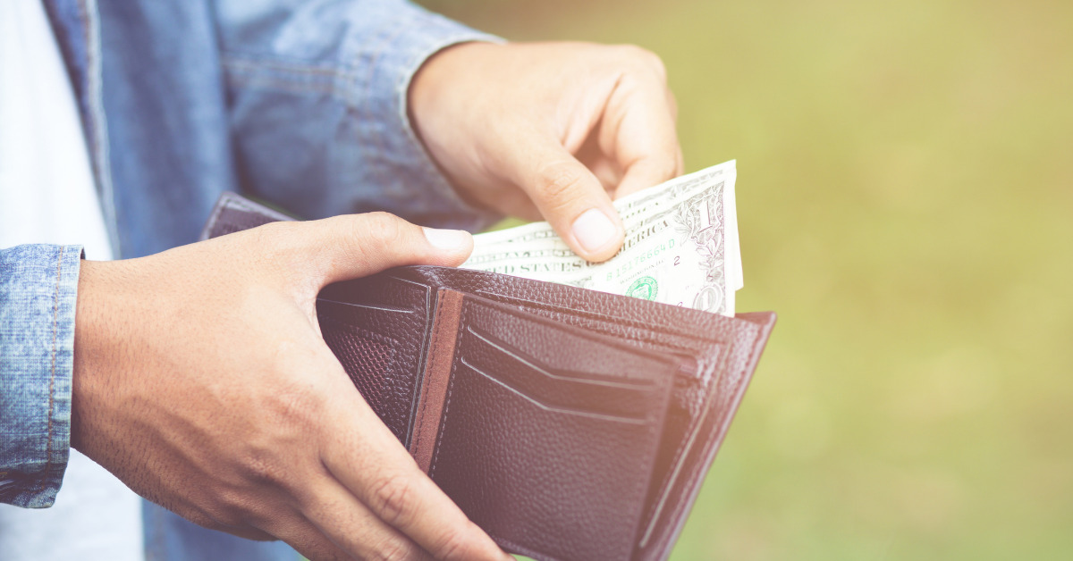 woman sifting through money in her wallet.