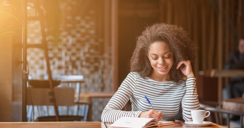 woman writing in her planner during life management challenge